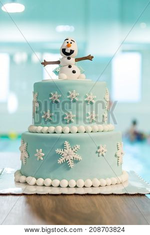 Christmas birthday cake with snowman and flakes close up