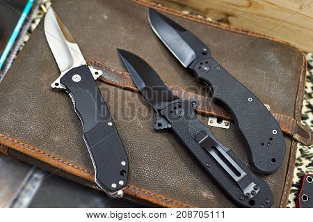 Folding Knives On Leather Retro Bag Tablet In Rarity Store