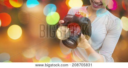 Smiling female photographer holding digital camera against defocused of christmas tree lights and fireplace