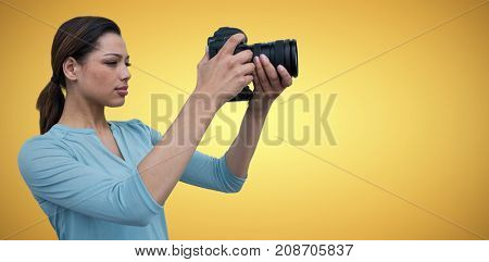 Young woman photographing through digital camera against yellow vignette