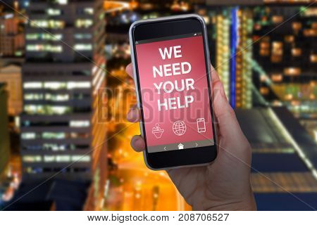 Hand holding mobile phone against white background against glowing road amidst building in city at night