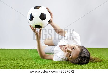 Beautiful Happy Girl In Sports Shirt Lying On Grass Holding Soccer Ball In Hands. Gray Background