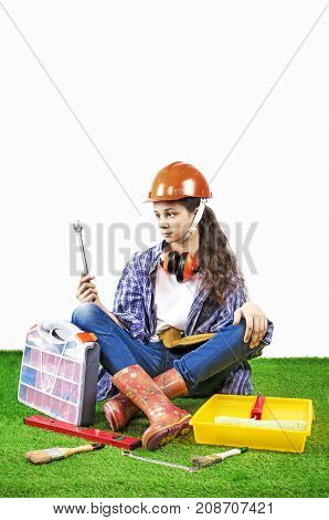 Girl builder holding a construction tools sitting on the grass