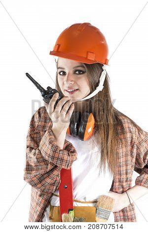 Beautiful girl in a helmet. Woman using Walkie Talkie and looking at the camera