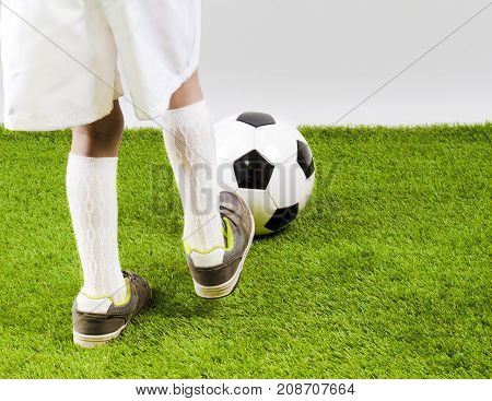 The soccer player's foot touches the soccer ball.