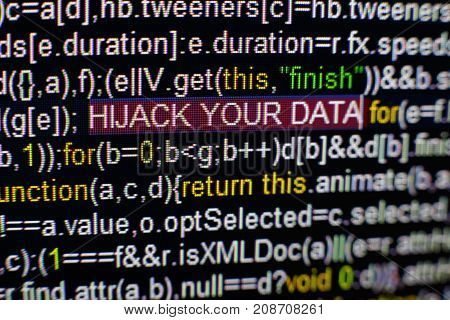 Macro photo of computer screen with program source code and highlighted HIJACK YOUR DATA inscription in the middle. Computer script on the screen with virus in it. Cyber security concept.