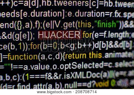 Macro photo of computer screen with program source code and highlighted HIJACKER inscription in the middle. Computer script on the screen with virus in it. Cyber security concept.