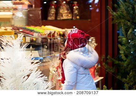 Children window shopping on traditional Christmas market in Germany on snowy winter day. Kids buying candy pastry and gingerbread in confectionery. Little girl choosing sweets in Xmas bakery.