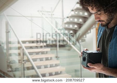 Young male photographer holding vintage camera against modern stairs in office building