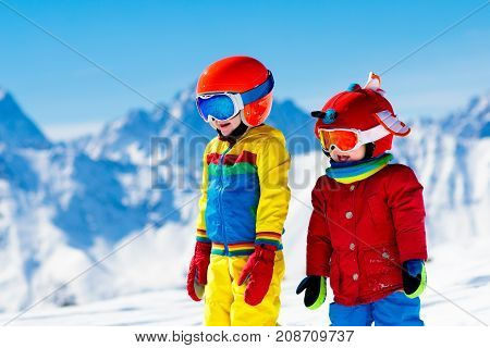 Child skiing in the mountains. Kid in ski school. Winter sport for kids. Family Christmas vacation in the Alps. Children learn downhill skiing. Alpine ski lesson for boy and girl. Outdoor snow fun.