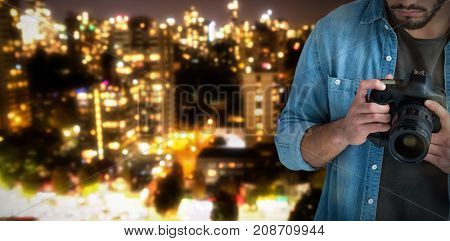 Male photographer operating camera  against defocused image of cityscape at night
