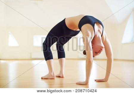 Beautiful woman practices backbend yoga asana Urdhva Dhanurasana - Upward facing bow pose in the yoga studio.