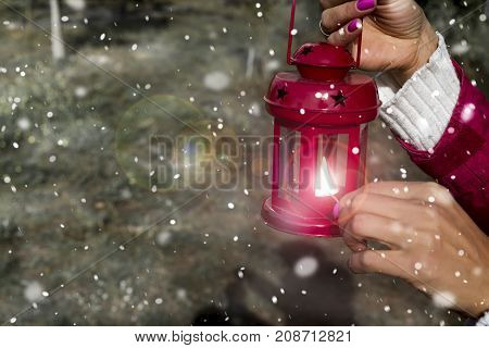 girl lights a candle Christmas red lantern on a winter evening outside