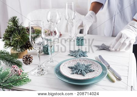 The process of serving the Christmas table. A woman is decorating a festive dinner table