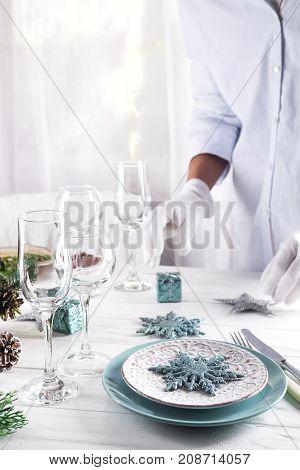 The girl serves a Christmas table. A festive Christmas table setting