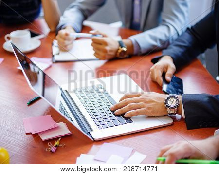 Hands of a businessman in a white shirt and gray jacket behind a laptop working on future ideas
