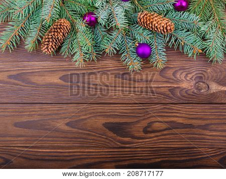 Winter concept of a green spruce branch on a brown wooden background with cones and three toys