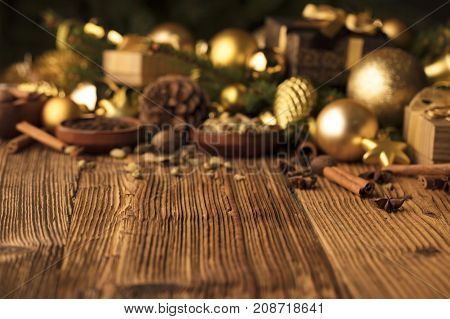 Christmas decoration in golden and brownish aesthetics with presents in boxes, golden baubles, christmas spices all on a rustic wooden background