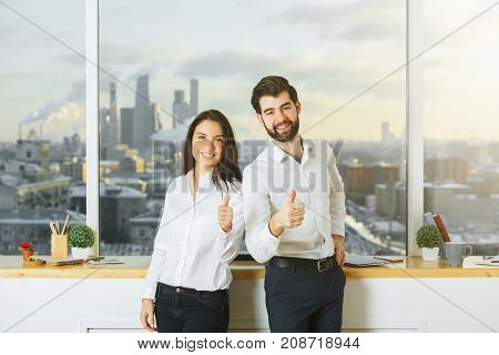 Young businessman and woman showing thumbs up in modern office interior with blurry city view and items on windowsill. Success concept