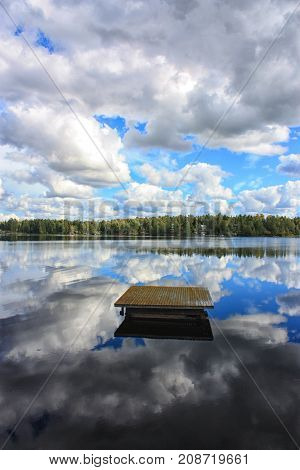 Tranquil landscape at the lake with the blue sky white clouds and a forest reflected symmetrically in the clean blue water