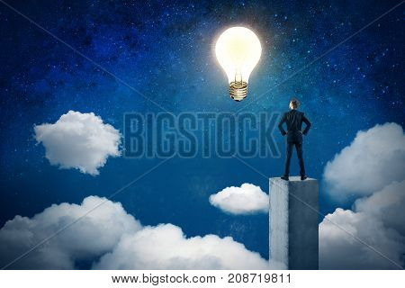 Back view of young businessman standing on concrete pedestal and looking at abstract glowing lamp in night sky. Idea and innovation concept