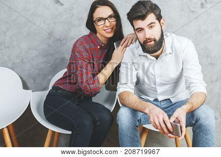 Attractive man and woman with cellphones sitting on chairs. Concrete wall background. Communication concept
