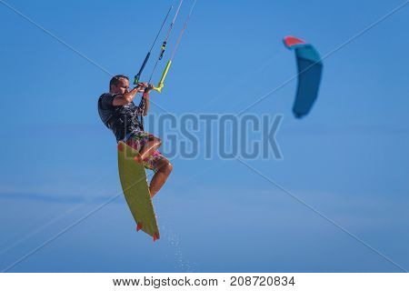 Young Atletic Man Riding Kite Surf On A Sea