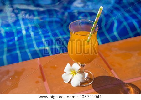 Glass Of Fresh Cool Orange Juice Drink With Flower On Border Of A Swimming Pool