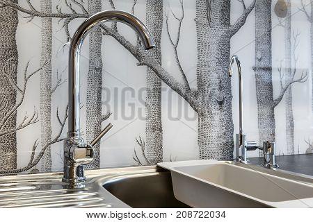 Detail of modern kitchen -sink and wooden wallpaper