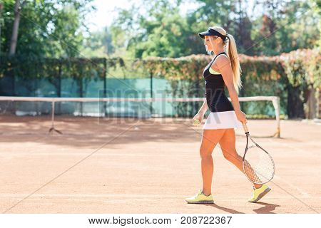 Beautiful tennis player, goes to the tennis court with a racket. In full growth. The concept of sport.