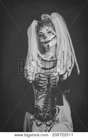 scary halloween woman with sugar skull makeup offering  candy mushrooms studio shot bw