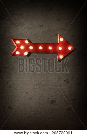 Lighted Red Marquee Arrow on a cement wall