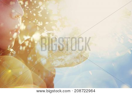 Child blowing snow into the sunlight