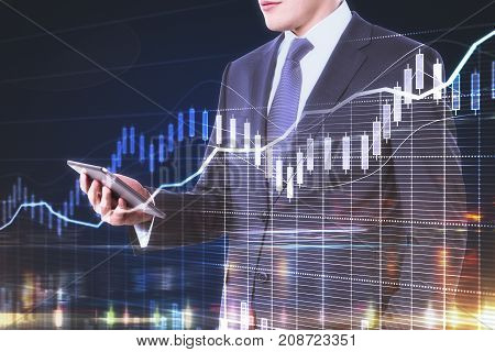 Side view of young businessman using device with forex chart on abstract night city background. Finance concept. Double exposure