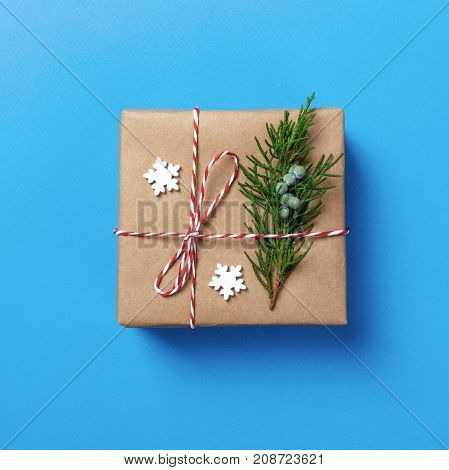 Craft paper wrapped present box craft rope bow ribbon on blue background top view.