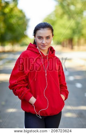 Sports girl in red uniforms listening to music on the phone for jogging