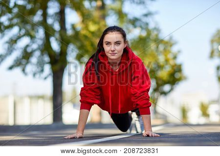 Sportive girl in red uniform on jogs, listening to music outdoors on a sunny day doing push-ups