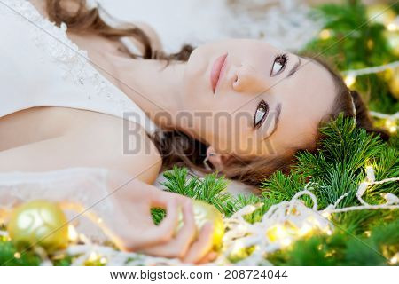 Young beautiful bride lying in spruce branches and garland lights.