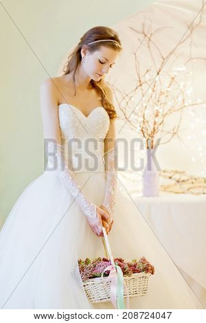 Young beautiful bride holding a basket with flowers.