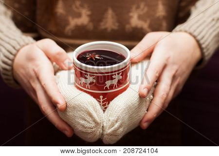couple holding swedish glogg or mulled wine in hands. Deer moose pattern on a background.