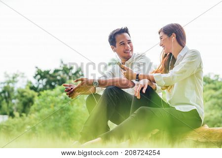 Young Asian lovely couple or college students sit listening to song music on smartphone together in park. Leisure activity Online love internet dating app technology or casual lifestyle concept