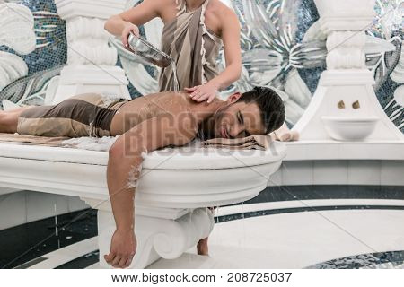Relaxed young man lying down on hot marble bed during traditional Turkish bath at luxury spa and wellness center