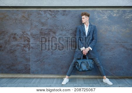 Businessman in gray coat. Standing against the wall, legs wide apart. The concept of career and entrepreneurship. In full growth.