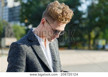A young guy in the city wearing glasses, dropped his head down. Close-up.