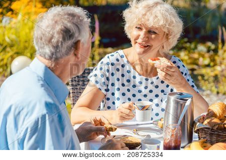 Happy elderly woman and man eating breakfast sitting in their garden outdoors in summer, eating bread rolls and drinking coffee