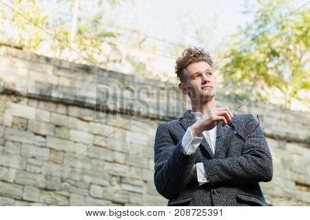 Businessman in gray coat. Standing against the wall background, hands clasped. The concept of career and entrepreneurship. Close-up. Bottom view.