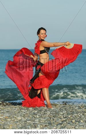 Dancer woman in black and red suit with fan dancing on seashore