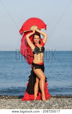 Dancer woman in black and red suit with fan dancing on seashore, fan overhead
