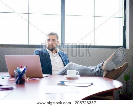 A businessman with a beard in an expensive suit threw his legs on the working table to relax