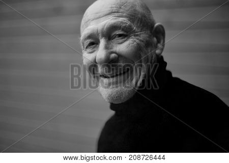 Black and white horizontal capture of handsome happy senior expressing positivity and young soul playing with camera and laughing. Old senior man closeup portrait. People feelings human concept.